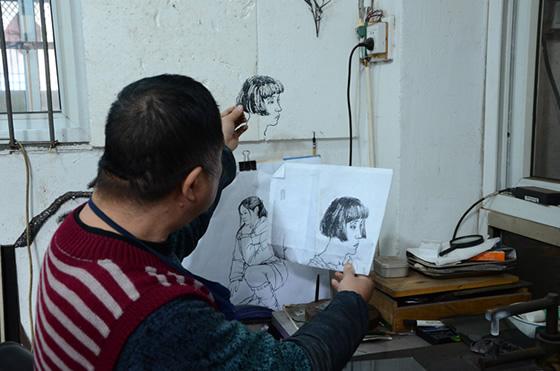 徽艺坊铁画大师凌晓华正在对比打制的人物像